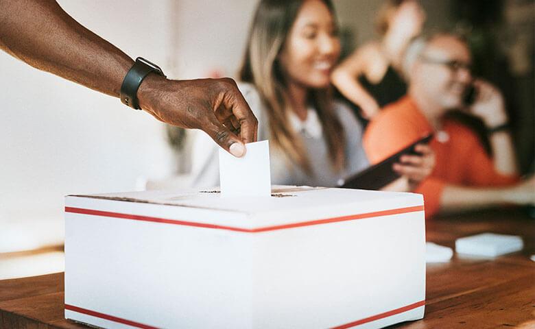 Main soumettant leur vote dans une urne