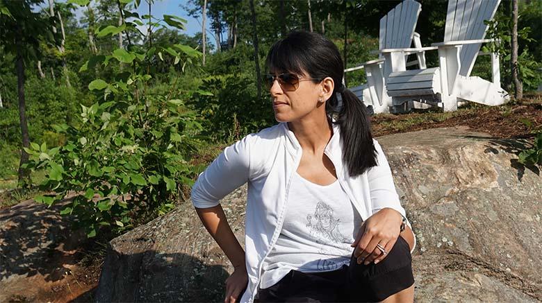 Photo de la Dre Soania Mathur assise à l'extérieur sur un gros rocher